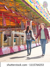 Happy beautiful tourist couple visiting funfair amusement park rides, walking holding hands, joyful smiling outdoors activities. Day out fun, holiday leisure recreation lifestyle, colorful exterior.