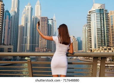 Happy beautiful tourist woman in fashionable summer white dress and sunglasses shooting mobile phone in Dubai marina in United Arab Emirates. Luxury and comfortable tourism season in UAE.