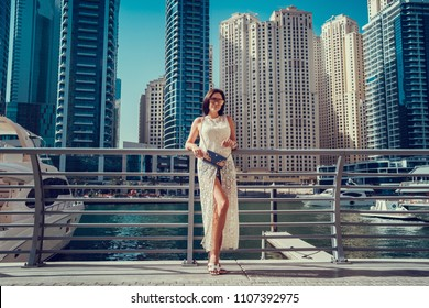 Happy beautiful unrecognizable tourist woman in fashionable summer white dress enjoying in Dubai marina in United Arab Emirates. Luxury and comfortable tourism season in UAE.