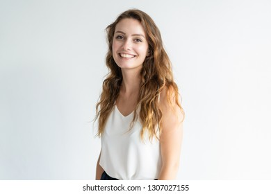Happy beautiful wavy-haired woman posing at camera. Smiling lady standing and looking at camera. Beautiful woman concept. Isolated view on white background.