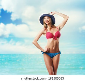 Happy Beautiful Woman In Bikini and hat on the Beach. Smiling. Holding the hat