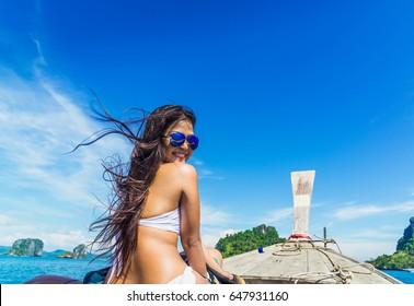 Happy beautiful woman in bikini on the boat at sunshine time, Andaman sea, Krabi, Thailand
