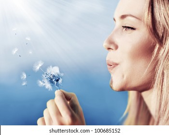 Happy beautiful woman blowing dandelion over sky background, having fun and playing outdoor, teen girl enjoying nature, summer vacation and holidays, young pretty female holding flower, wish concept
