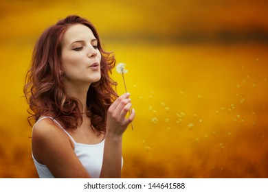 happy beautiful woman blowing dandelion in the field
