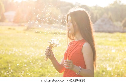 Happy beautiful woman blowing dandelion over sky background, having fun and playing outdoor, enjoying nature, summer vacation and holidays, young pretty female holding flower