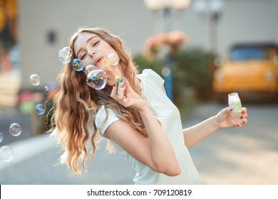 happy beautiful woman blowing soap bubbles outdoor
