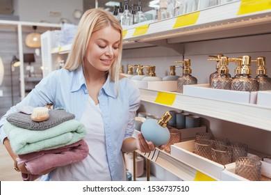 Happy beautiful woman buying bathroom goods at homeware store, copy space