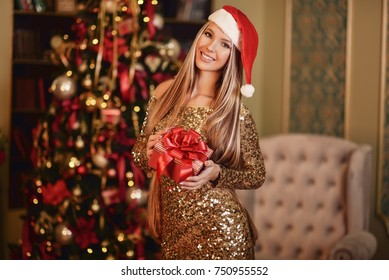 Happy beautiful woman dressed in evening golden dress standing in front of a New Year tree holding a gift. Christmas concept.