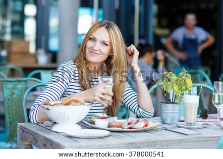 Happy beautiful woman drinking coffee with milk and having healthy breakfast in outdoor cafe in summer city in Europe.