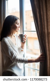 Happy beautiful woman drinking hot coffee looking on window at home in the morning
