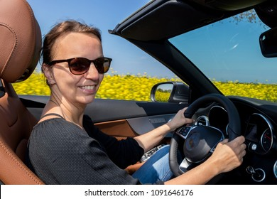 Happy beautiful Woman Driving in Luxury Convertible Sports Car