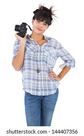 Happy beautiful woman with her hand on hip and holding camera on white background