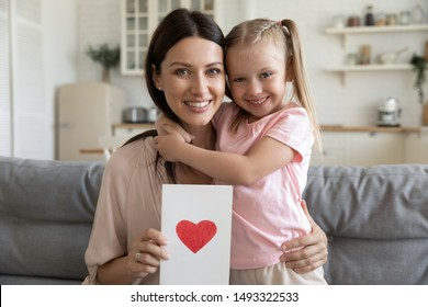 Happy beautiful woman holding postcard with drawn red heart embraces little daughter people sitting on couch at home looking at camera, concept of life events celebration, family holidays, mothers day