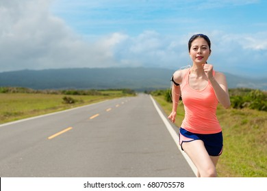 happy beautiful woman jogger running on road and workout body to train personal endurance in order to prepare marathon competition.