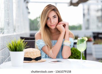 Happy beautiful woman with long hair blue gentle dress. Sits cafe table. Emotions tenderness lightness spring and summer. Tanned skin casual makeup. Waiting for lunch dinner order in restaurant.
