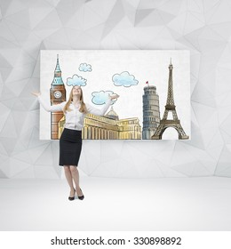 A happy beautiful woman is looking up and dreaming about the visiting of the most famous European cities. Sketches of European cities are drawn on the whiteboard. Contemporary wall.