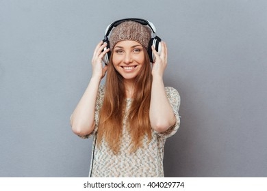 Happy beautiful woman lstening music in headset and looking at camera