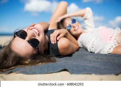 Happy beautiful woman lying on blanket on beach with friend