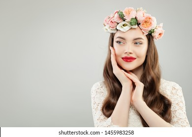 Happy beautiful woman on gray banner background. Pretty girl with clear skin, long shiny hair and flowers