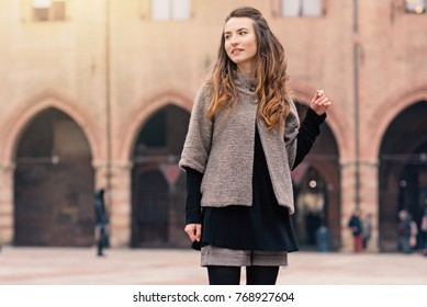 Happy beautiful woman portrait outdoors in Piazza Maggire, Bologna, Italy. Natual flare.
