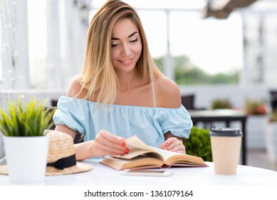 Happy beautiful woman reading paper book. Long hair blue gentle dress. Sits cafe table. Emotions tenderness lightness spring summer. Tanned skin casual makeup. Waiting lunch dinner order restaurant.