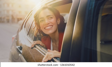 Happy Beautiful Woman Riding on a Back Seat of a Car, Looks out of the Open Window in Wonder. Traveling Girl Experience Magic of the World. Shot Made from Outside the Vehicle.