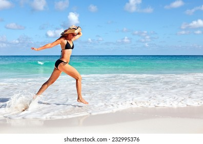 Happy beautiful woman running on the beach. Caribbean vacation