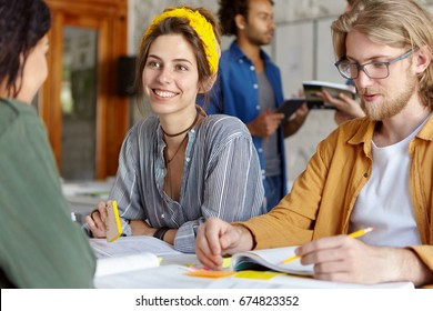 Happy beautiful woman in shirt discussing something with her African friend sitting near her groupmate with beard. Team of young people working together using books. Communication and team concept