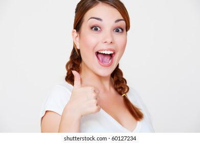 happy beautiful woman showing thumbs up over grey background