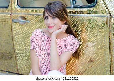 Happy Beautiful Woman Sitting Against Gold Retro Car.