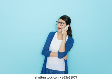 happy beautiful woman standing in blue wall background and using mobile cell phone calling for friend chatting on freedom time.