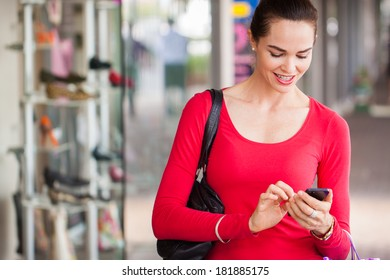 happy beautiful woman texting on a mobile or smart phone whilst out shopping.