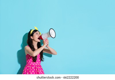 happy beautiful woman using megaphone speaking information and wearing pink cute dress in blue wall background.
