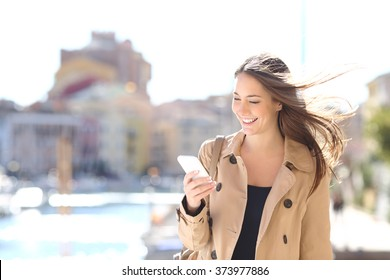 Happy beautiful woman walking and writing or reading sms messages on line on a smart phone while the wind moves her hair in a street of a port