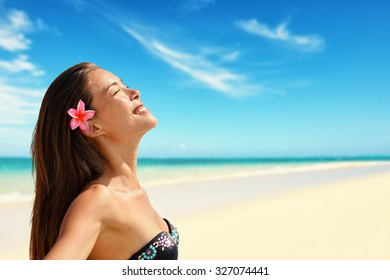 Happy beautiful woman wearing flower while enjoying sunlight at beach. Mixed race Asian / Caucasian female is with eyes closed. She is on summer vacation.