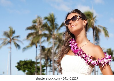 Happy beautiful woman wearing flowers while enjoying sunlight at the beach. She is on summer vacation. Woman wearing traditional Hawaiian lei on Oahu, Hawaii, USA.