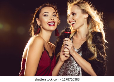 happy beautiful women singing with microphone in karaoke