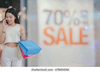Happy beautiful young asian woman doing shopping