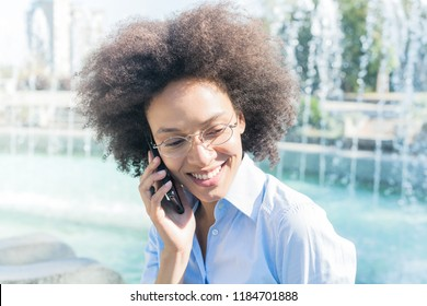 Happy Beautiful Young Black Woman With Glasses Using Smartphone. Outdoor Portrait, Casual Wear , Looking At The Side