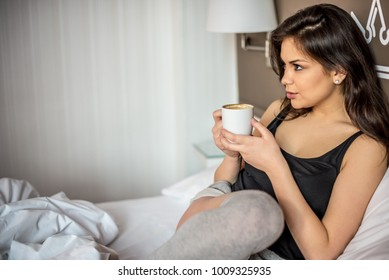 Happy beautiful young brunette woman relaxed smiling in bed drinking coffee