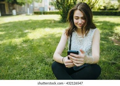 Happy beautiful young Caucasian girl with smart phone outdoors o