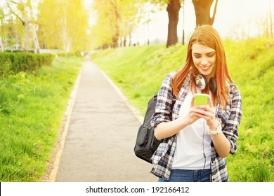 Happy beautiful young Caucasian redhead high school girl with green smart phone outdoors on sunny summer day texting and smiling.