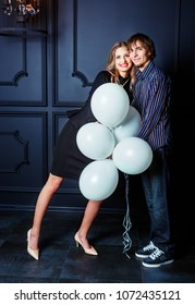 happy beautiful young couple against studio background with white balloons