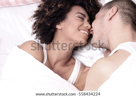 Happy beautiful young couple having fun in bed, smiling.