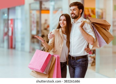 Happy beautiful young couple holding shopping bags, looking upon showcase and smiling while standing in mall