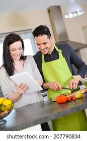 happy beautiful young couple preparing organic vegetables salad for lunch together in kitchen for summer party