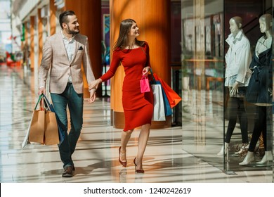 Happy beautiful young couple with shopping bags in mall