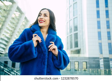 Happy Beautiful young cute woman in blue vegan and faux fur coat is posing on urban city background. Fashion trendy style clothes