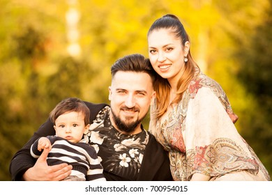 Happy beautiful young family with her son in a walk in the park. Family spending quality time together
