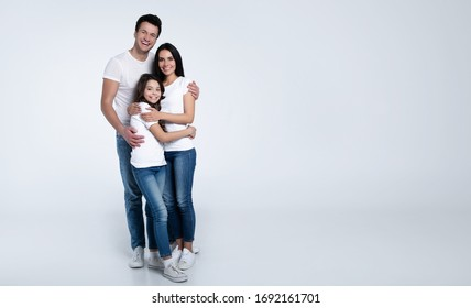 Happy beautiful young family in white t-shirts while they hugging each other isolated on a light background.